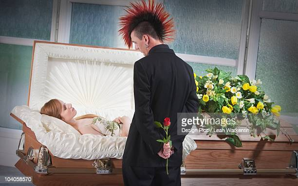 A Man Holding A Rose And Viewing A Deceased Woman Laying In A Coffin
