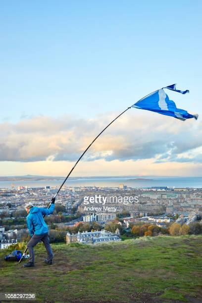 Man holding a Scottish Flag on a long pole in strong wind on top of Salisbury Crags with view of Edinburgh