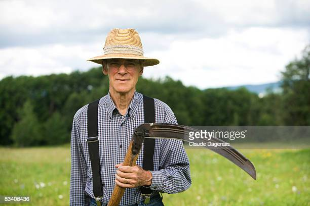 Man holding a scythe in the middle of a field.