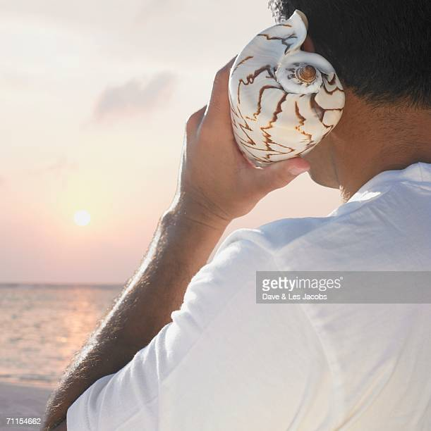 Man holding a seashell to his ear