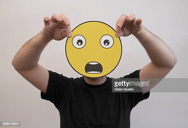 Man holding a shocked emoticon face in front of his face