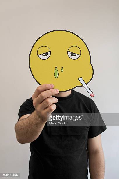 Man holding a sick emoticon face in front of his face