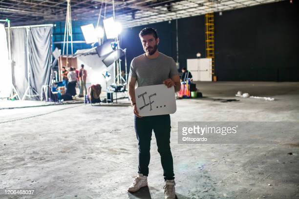 man holding a sign of empowering self - film set stock pictures, royalty-free photos & images