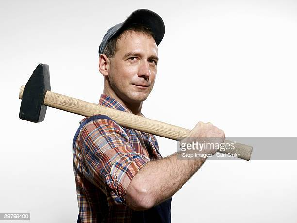 a man holding a sledgehammer over his shoulder - hammer stock pictures, royalty-free photos & images