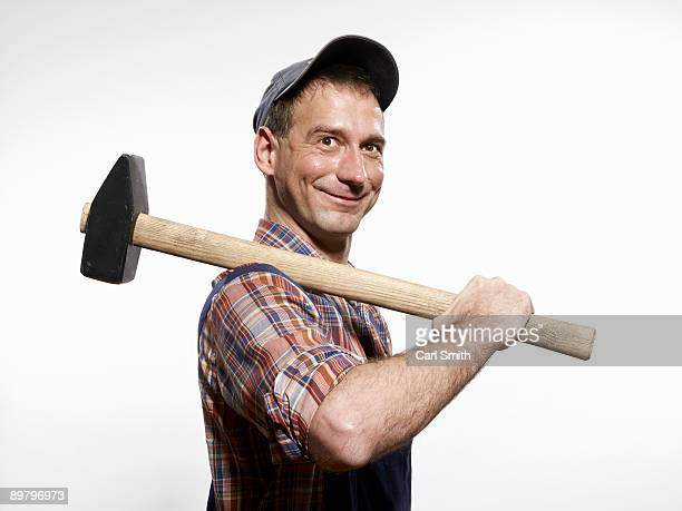 a man holding a sledgehammer over his shoulder - satírico fotografías e imágenes de stock
