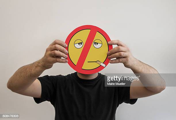 man holding a smoking emoticon face with a prohibited red line through it - no smoking sign stock pictures, royalty-free photos & images