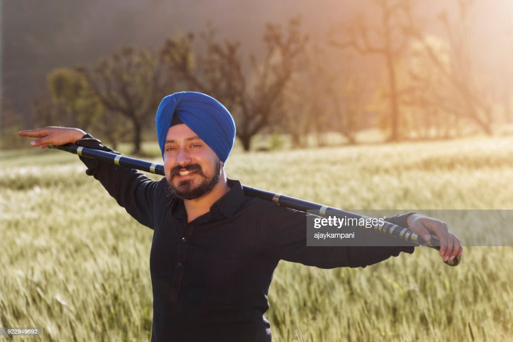 Man holding a stick and smiling in a field