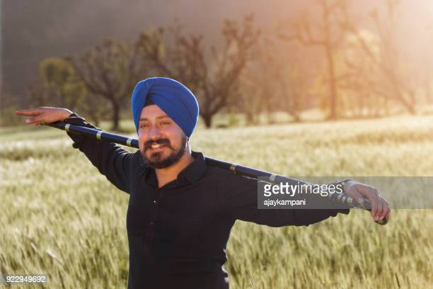 man holding a stick and smiling in a field - punjab india stock pictures, royalty-free photos & images