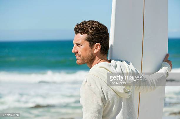 Man holding a surfboard on the beach