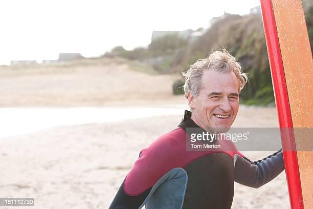 homme tenant une planche de surf - aventure photos et images de collection
