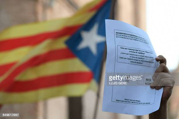 A man holding a symbollic ballot marked with a 'Yes' attends a protest against a search for propaganda supporting Catalonia's independence referendum...