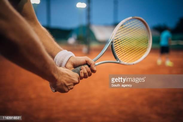 hombre sosteniendo una raqueta de tenis en tierra batida - tennis fotografías e imágenes de stock