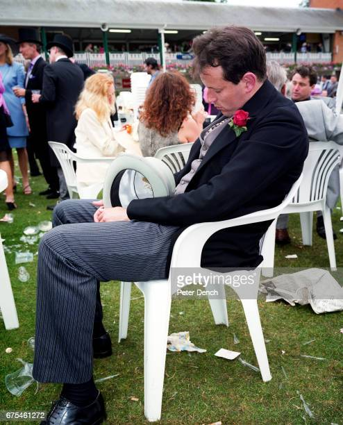 A man holding a top hat takes a nap in a white plastic chair at Royal Ascot June 2000