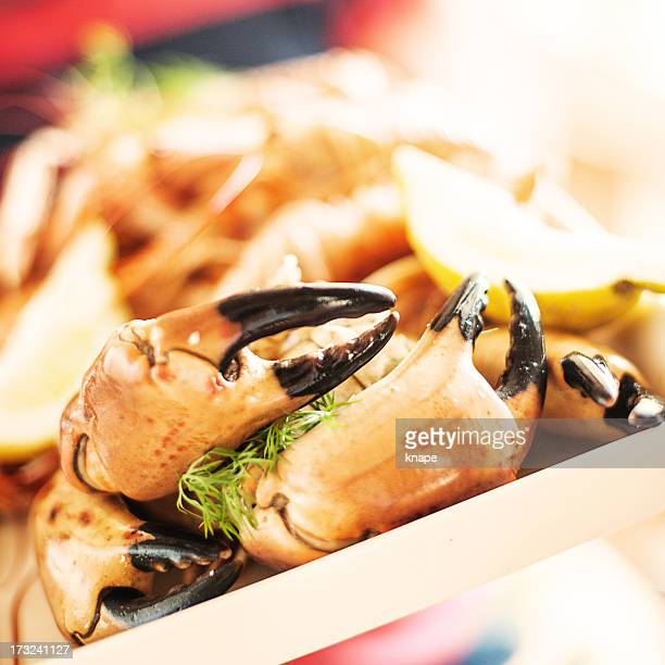 Man holding a tray of crab claws