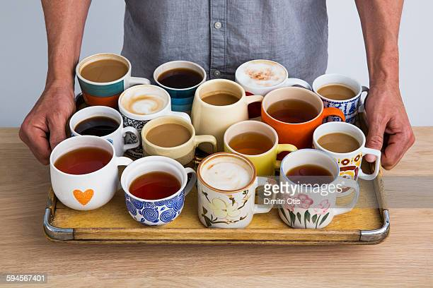 Man holding a tray of many cups of coffee and tea