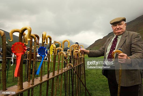 Man holding a walking stick after prize giving