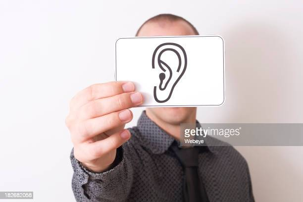 Man holding a white card with an ear drawing over his face