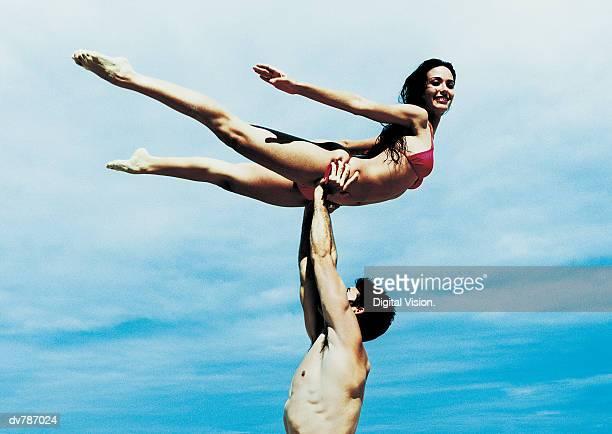 Man Holding a Woman in a Bikini