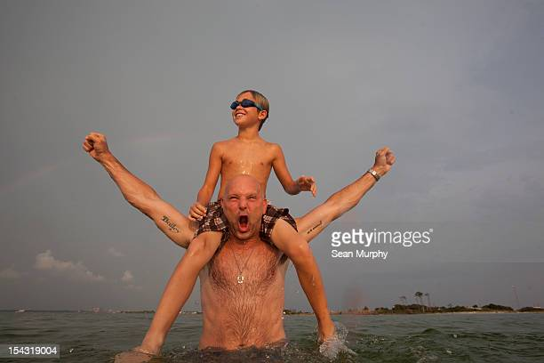 Man Holding a Young boy on his shoulders in ocean