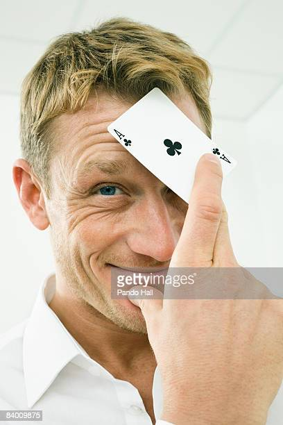 Man holding Ace of clubs playing card, smiling