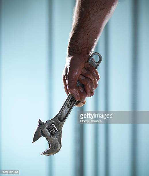Man holding adjustable spanner with oil dripping
