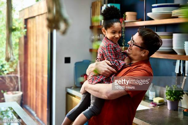 man holding adopted daughter in kitchen - genderblend stock pictures, royalty-free photos & images