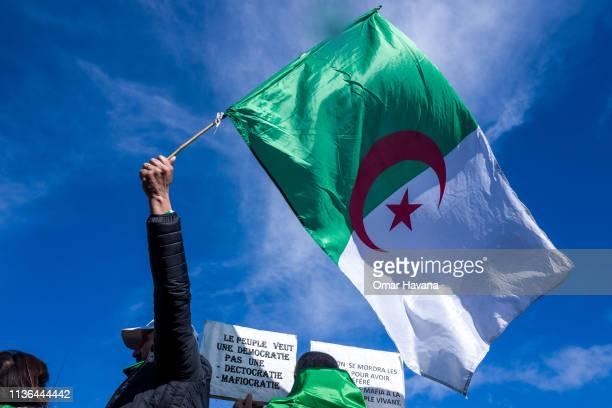 Man holding an Algerian flag shouts slogans during a demonstration against Algerian President Abdelaziz Bouteflika in Place de la République on March...