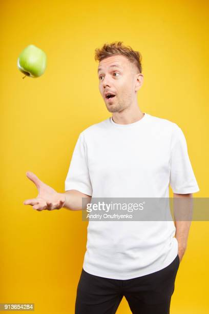 man holding an apple on color background - lanciare foto e immagini stock