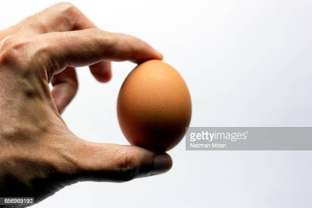 A man holding an egg. A food concept.