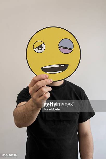 Man holding an emoticon face with a black eye in front of his face