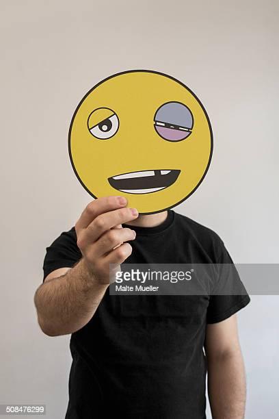 man holding an emoticon face with a black eye in front of his face - hombre golpeado fotografías e imágenes de stock