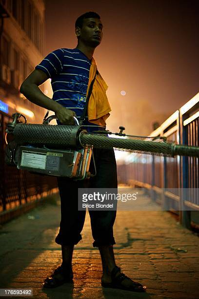 Man holding an impressive mosquito fumigating system in the streets of Dhaka, Bangladesh.