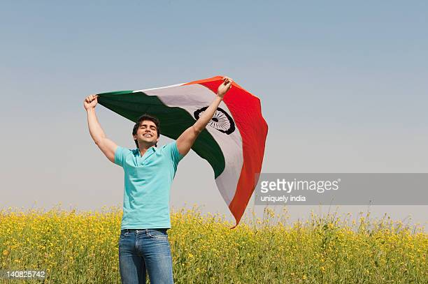 Man holding an Indian flag in an oilseed rape field