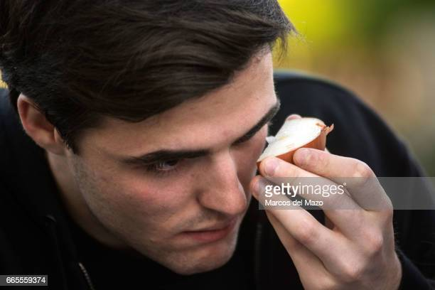 A man holding an onion near his eye trying to cry during an event organized through Facebook under the name 'Gathering for crying' celebrated in the...