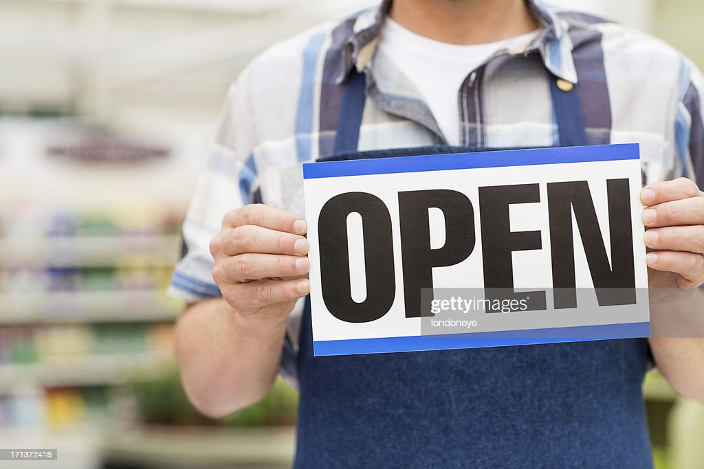 Man Holding an Open Signboard : Stock Photo