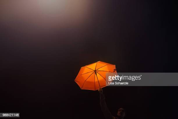 man holding an orange umbrella in the sky at night - shielding stock pictures, royalty-free photos & images
