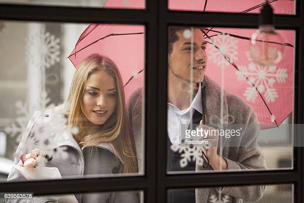 Man holding an umbrella for his girlfriend