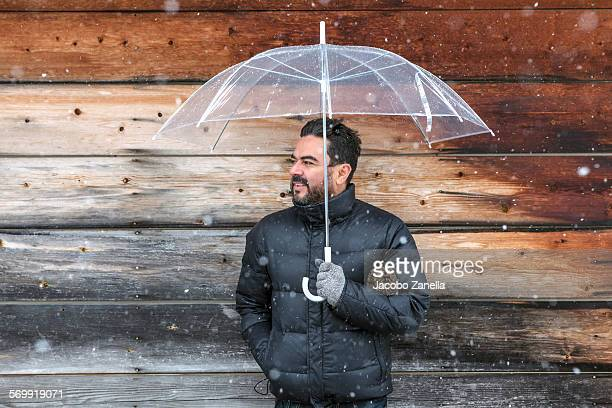 Man holding an umbrella in the snow