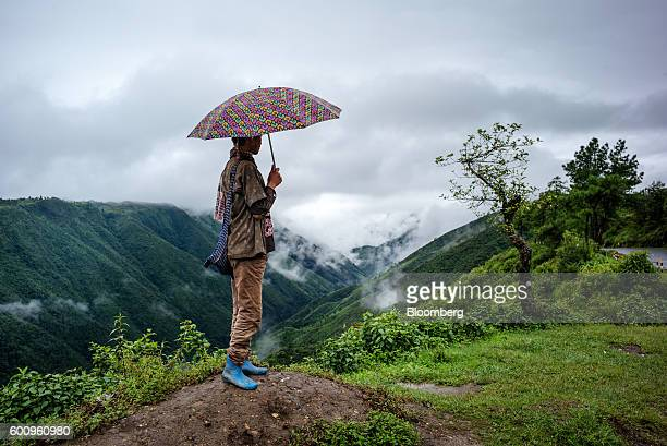 A man holding an umbrella waits for public transport by the side of a road in Cherrapunji Meghalaya India on Saturday Aug 13 2016 Two years of...