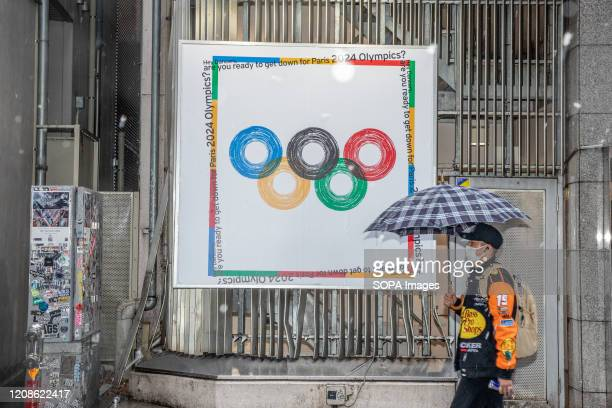 A man holding an umbrella walks by an Paris Olympic 2024 poster during the coronavirus pandemic in Shibuya The Tokyo metropolitan government has...
