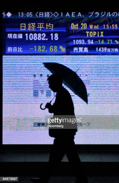 A man holding an umbrella walks past a video screen displaying the day's Nikkei 225 Stock Average in Tokyo on October 20 2004 The Nikkei lost 18268...