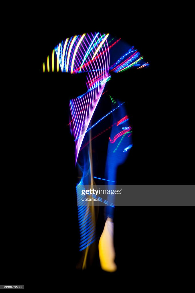 Man holding an umbrella with light trail texture : Stock Photo