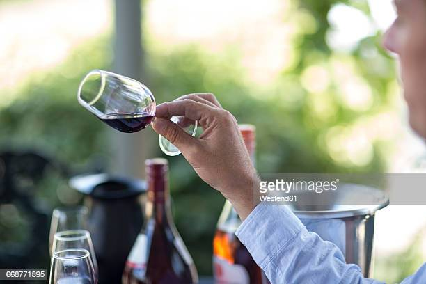 Man holding and judging glass of red wine