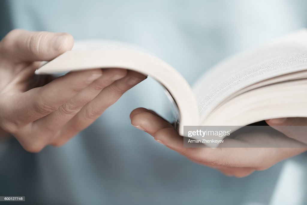 Man holding and reading book in library : Stock Photo