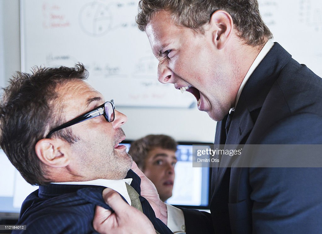 Man holding and shouting at co-worker : Stock Photo
