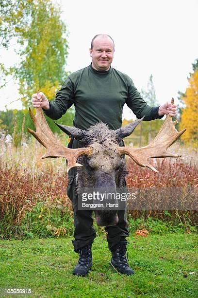 Man holding antler of dead moose