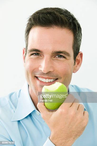 Man holding apple and smiling, close-up