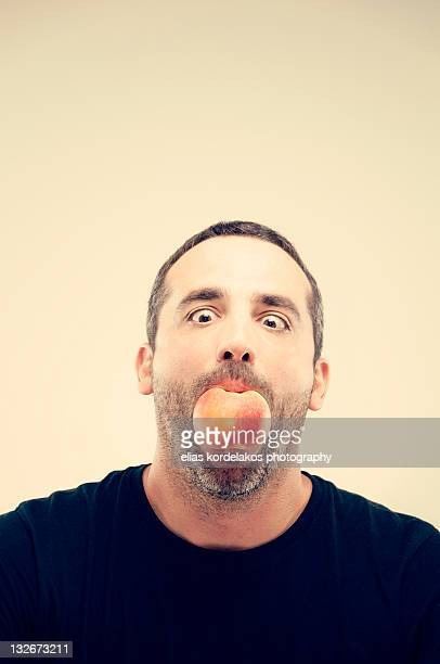 man holding apple in his mouth - くわえる ストックフォトと画像