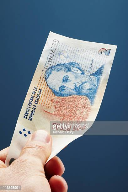 Man holding Argentinian two Pesos note