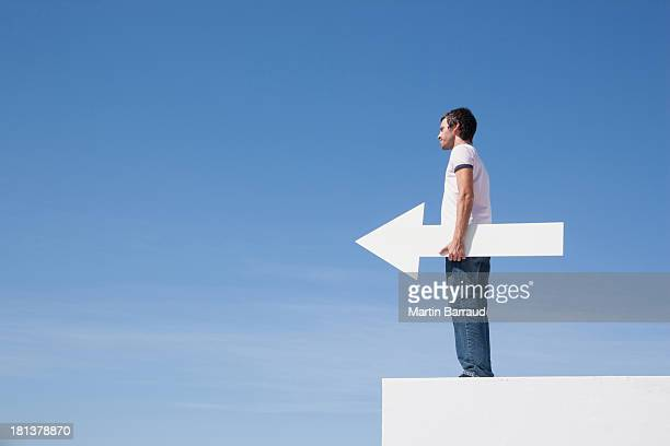 Man holding arrow on pedestal outdoors